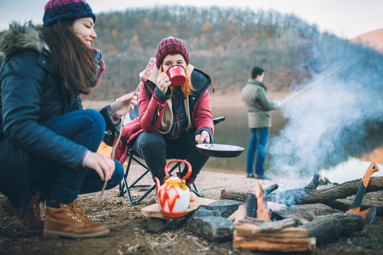 Two women sitting around a fire drinking hot tea while camping in winter.