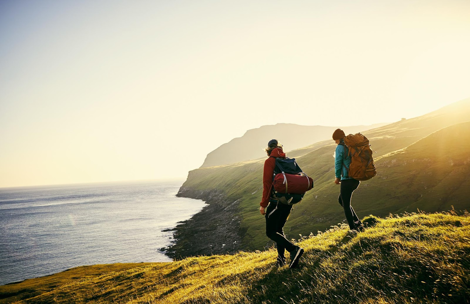 Two people hiking by the sea in the UK.