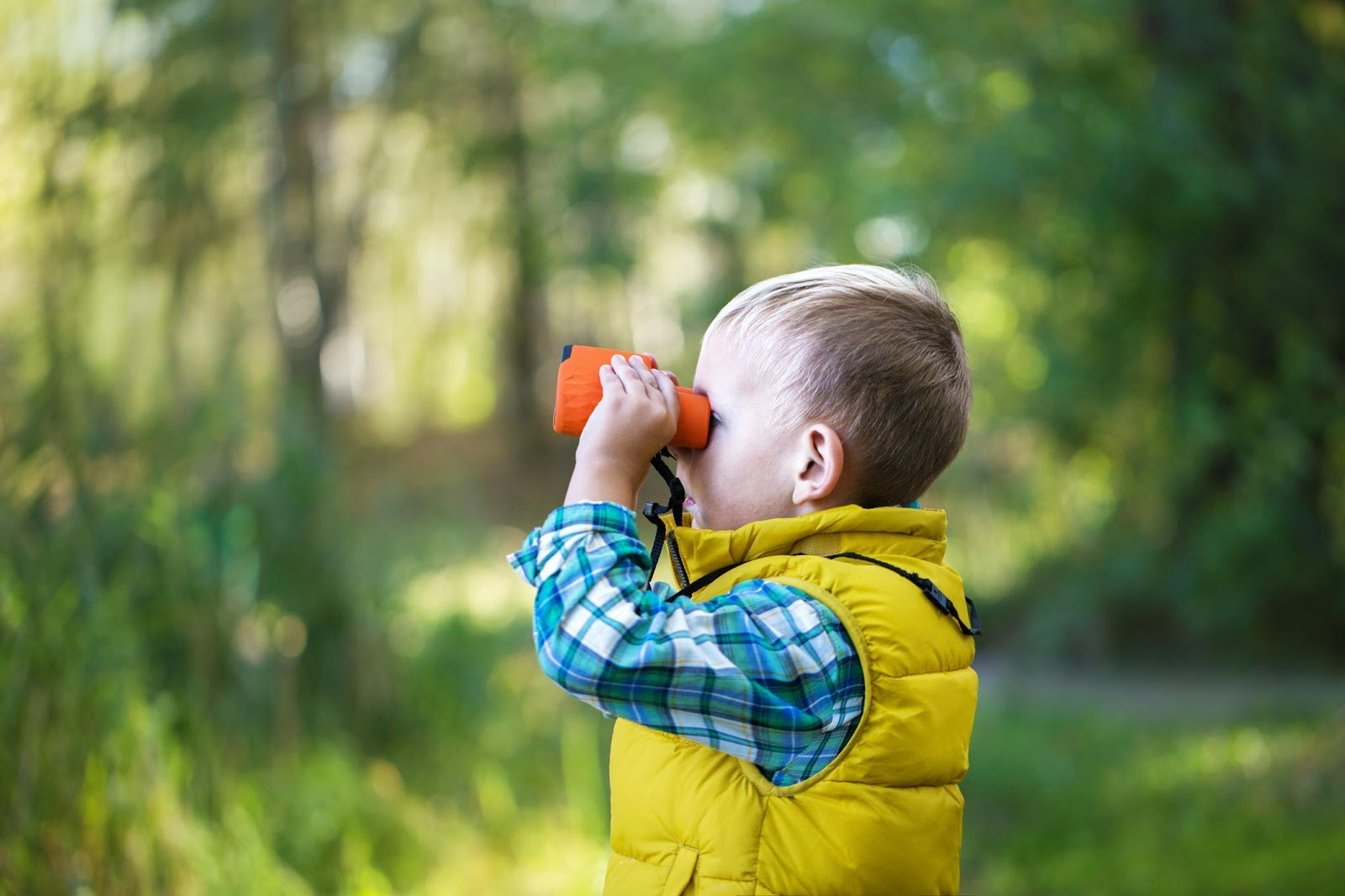 Little boy wearing a yellow gilet holding up binoculars.
