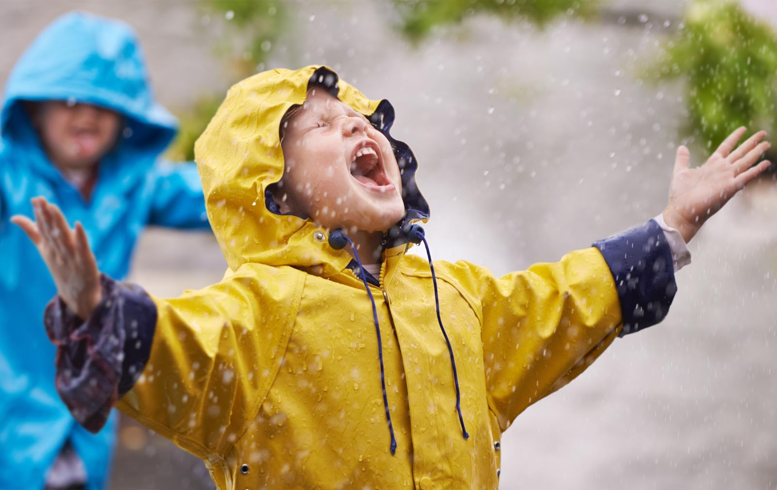 A child in a yellow raincoat standing in the rain with his arms up.