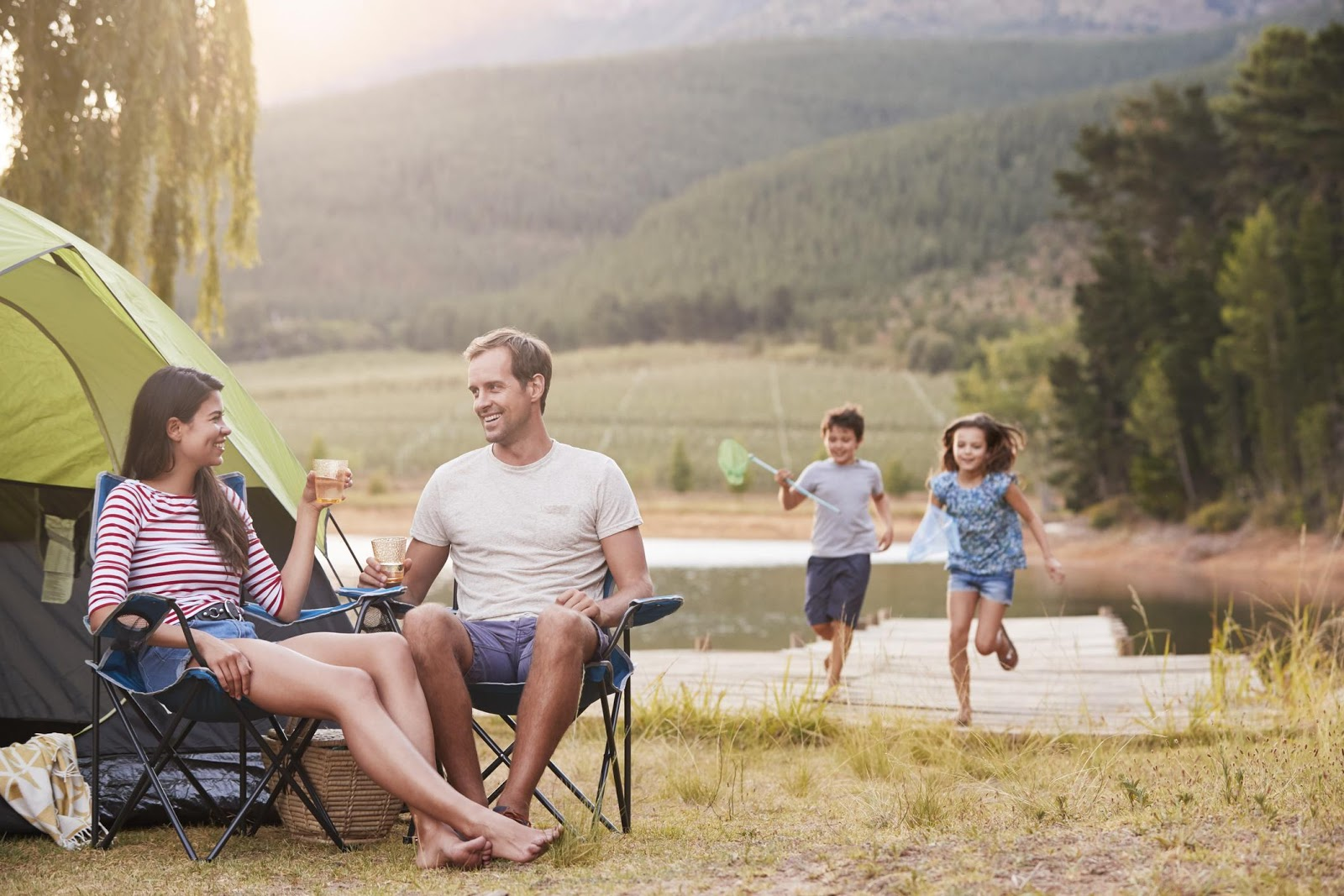 Couple in their shorts and t-shirts camping while children run in the background