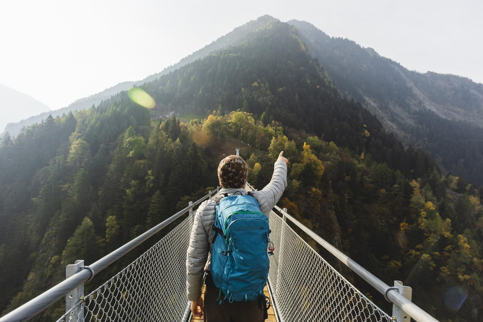 Hiker walking across a bridge with a blue backpack on.