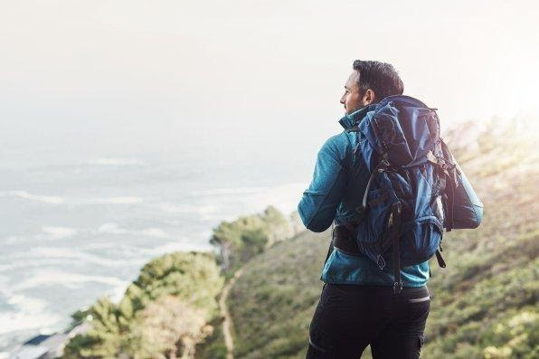 Man staring out over the view with a backpack on.