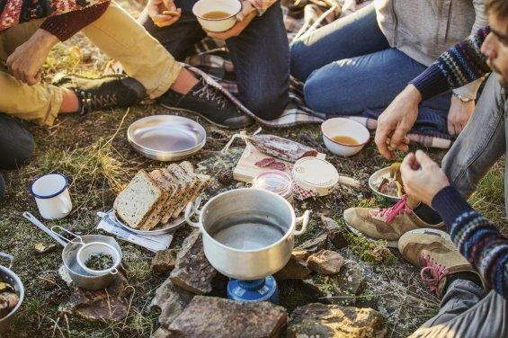 Group of friends gathered around the camping stove cooking breakfast.