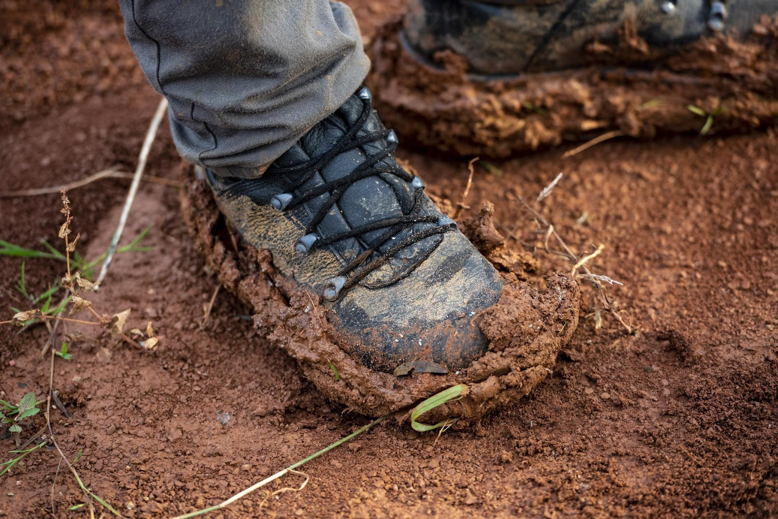 Person standing in thick mud with their walking boots on.