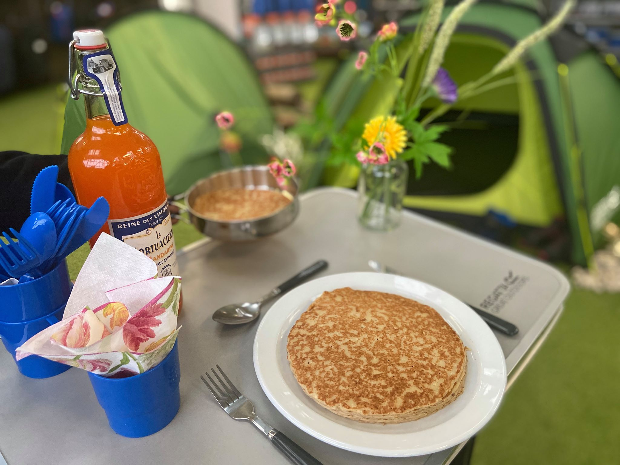 Stack of pancakes at breakfast table outside.