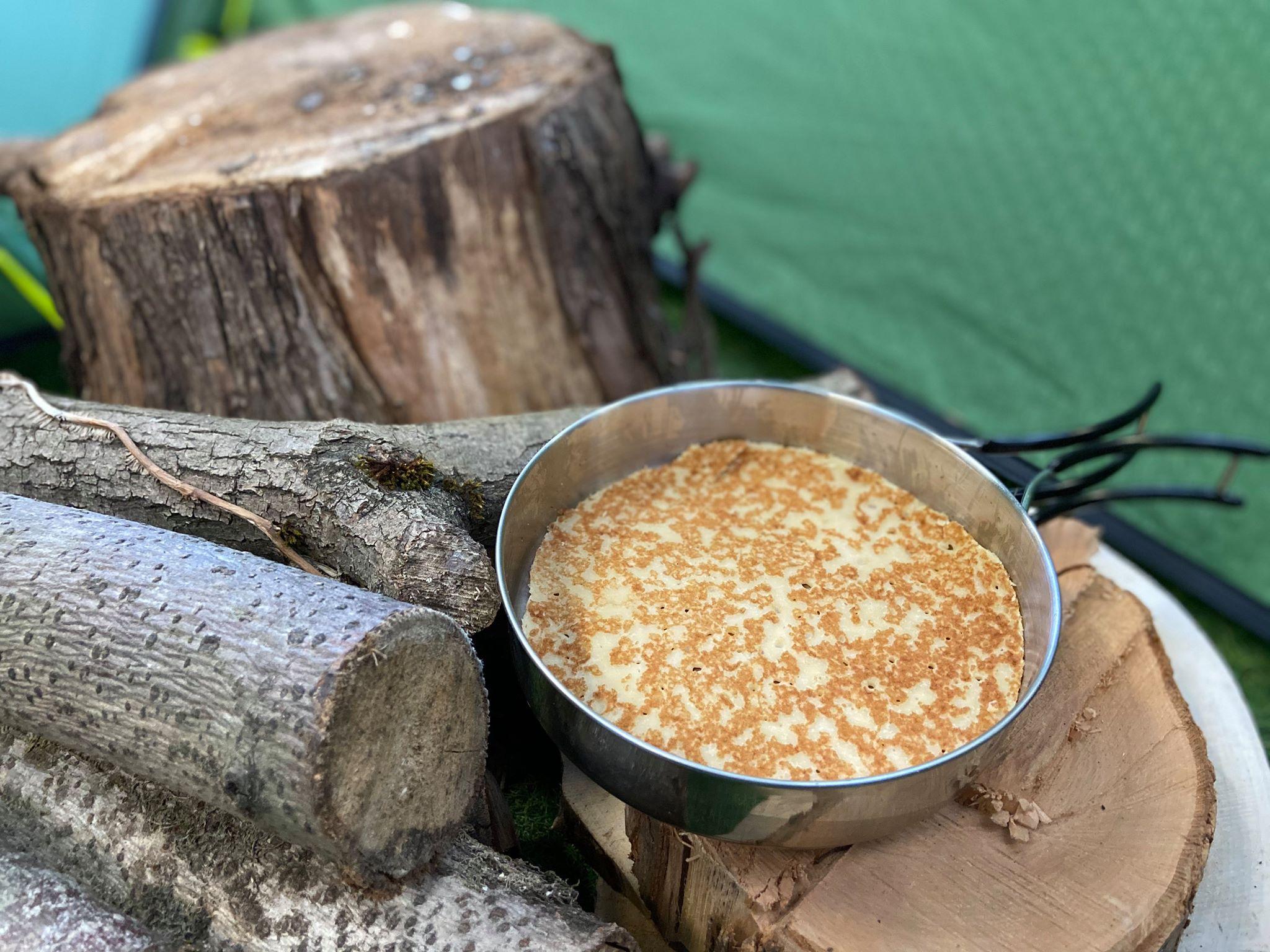 Pancake in a pan on top of logs.