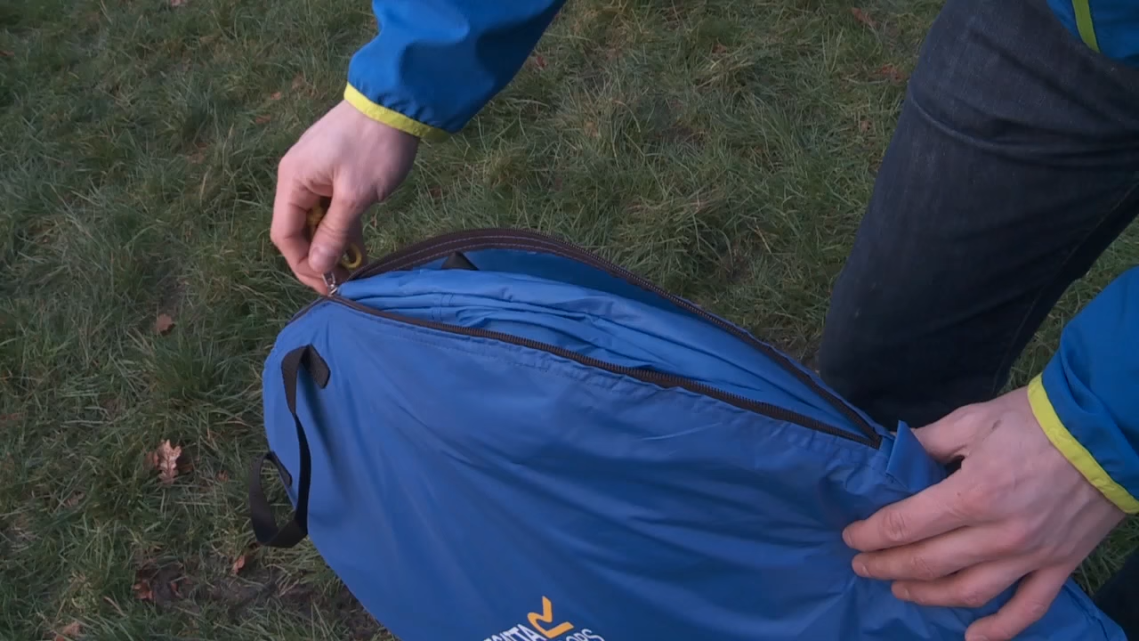 A man with a folded pop up tent inside a carrier bag.