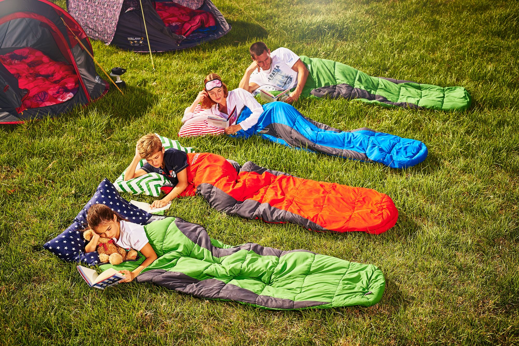 Family lay down on grass inside sleeping bags.