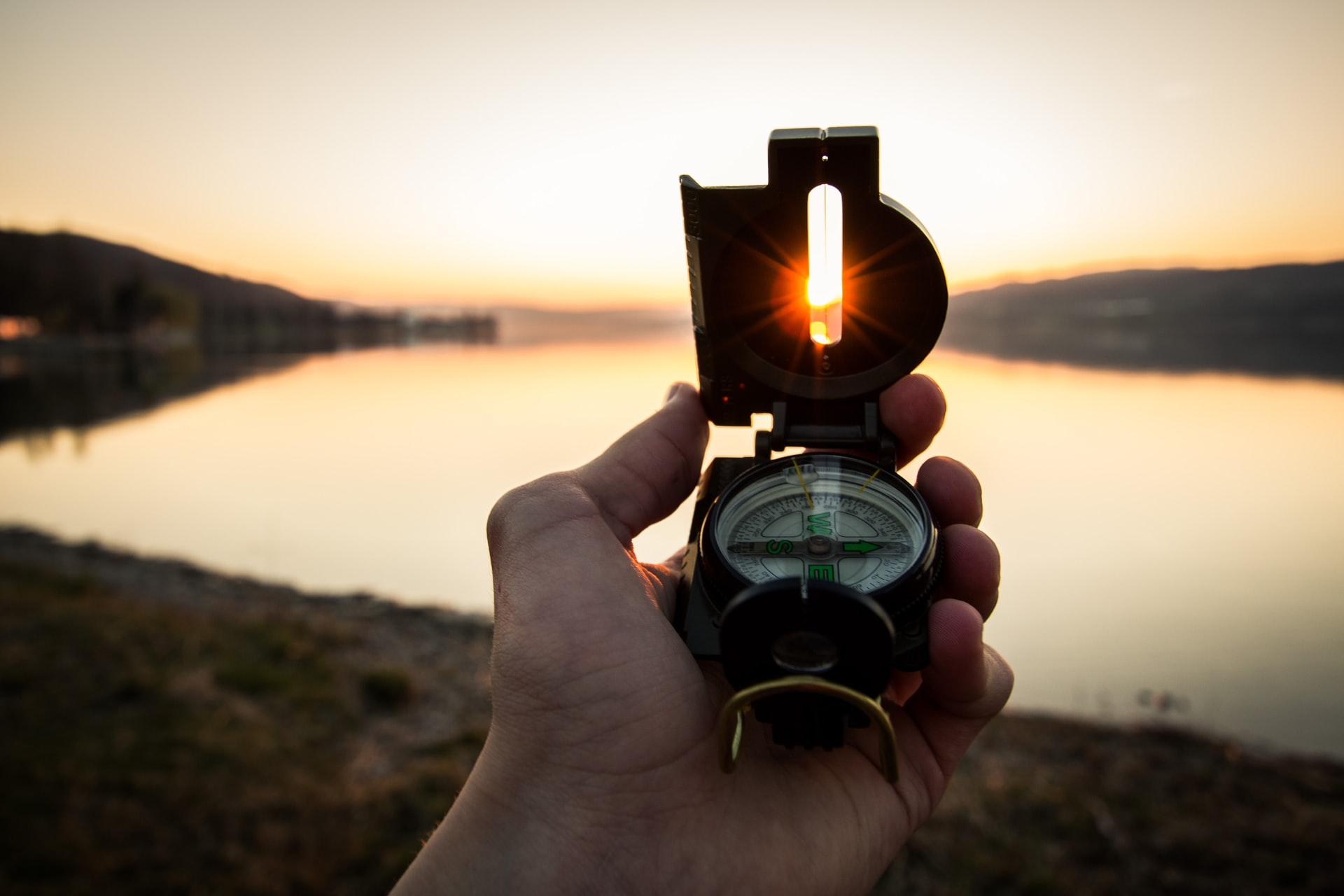Hand holding a compass to the sunset.