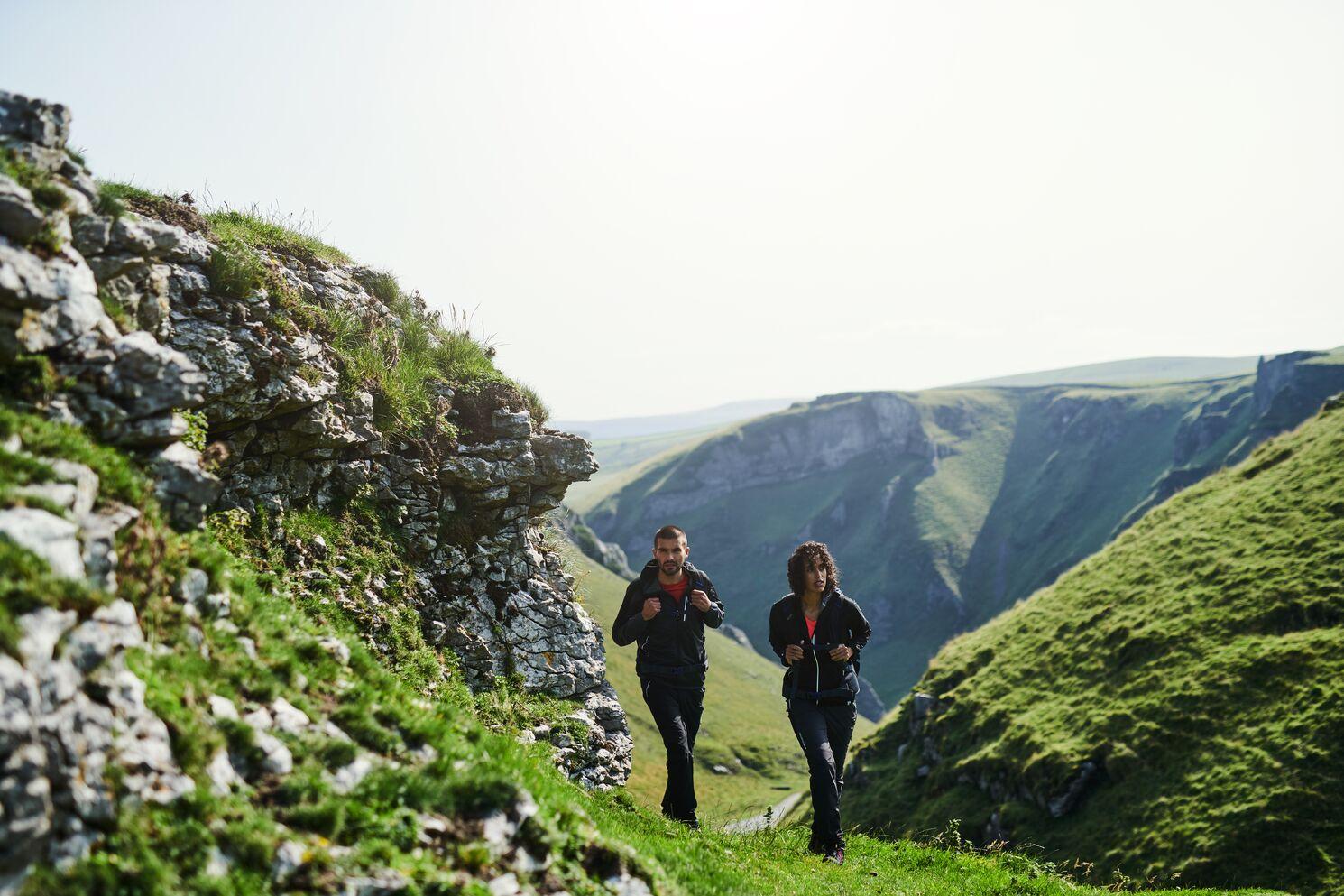 Couple walking through green hills.