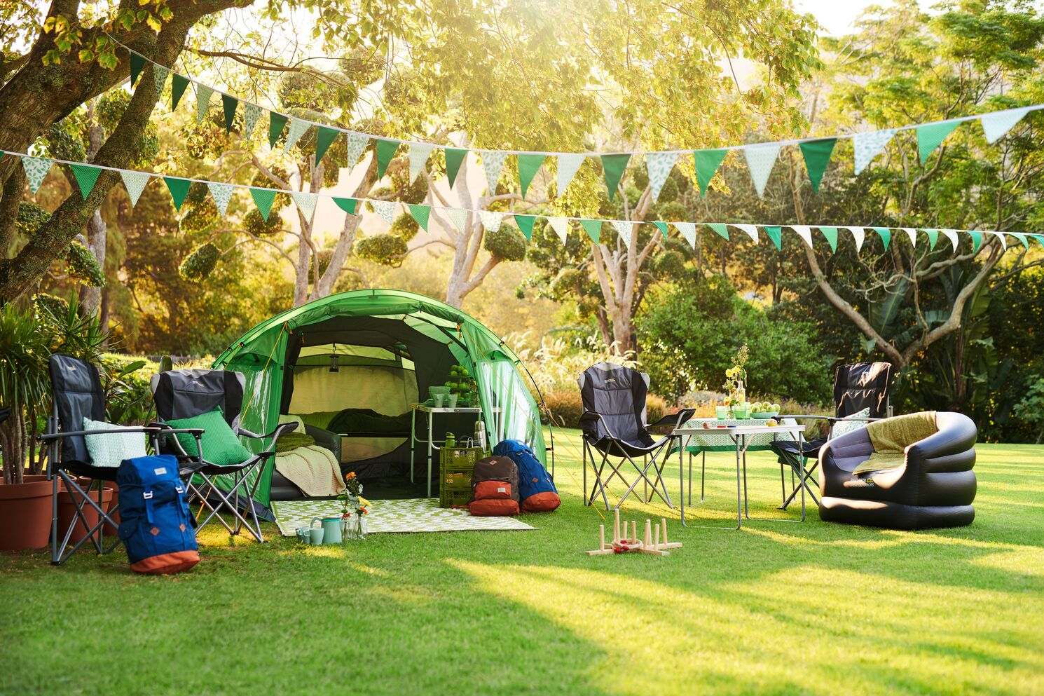 A full family camping setup, including a tent, camping furniture and kids games.