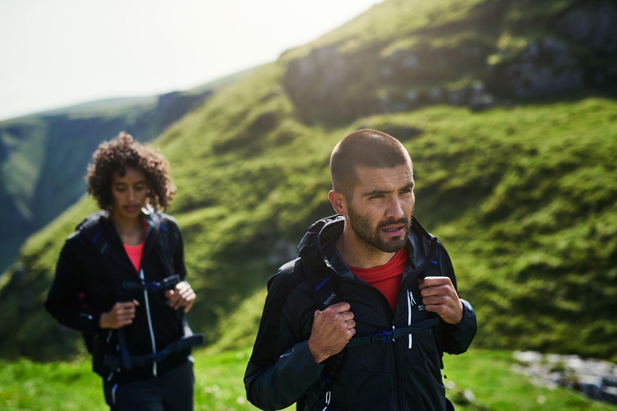 Man and women walking in the hills wearing softshell jackets.