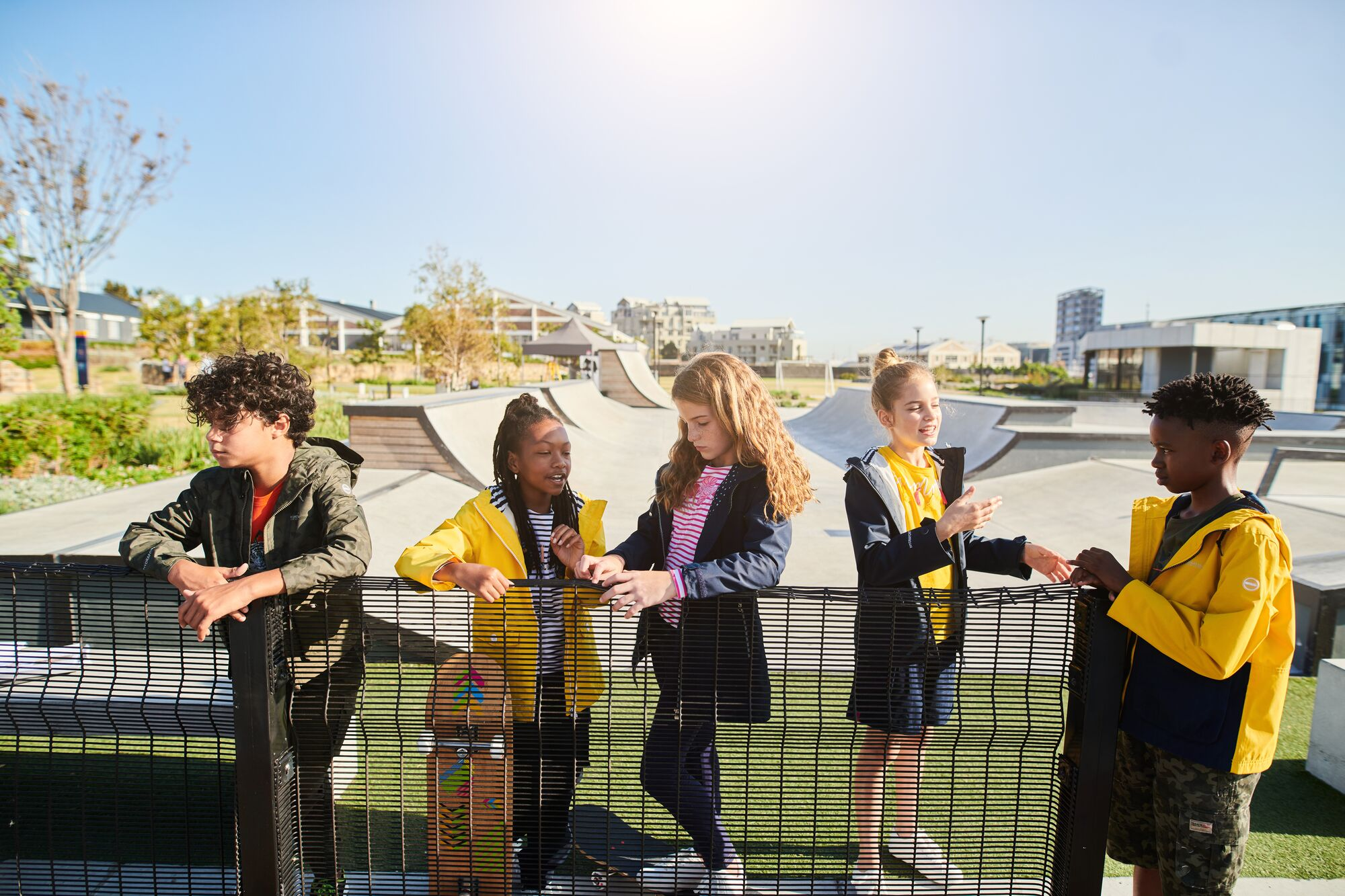Group of 5 school children at the playground wearing yellow raincoats